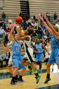 Puffers' Camaryia Williams takes the ball strong to the basket against Shores' Kelsey Wolffis (12).  Photo/Eric Sturr
