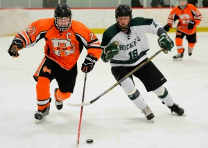 Reeths Puffer's Kevin McCrary (18) and Rockford's Brock Johnson (21) battle for the puck.  Photo/Eric Sturr