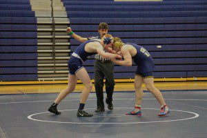 Mona Shores' Nick Brown (left) battles Grand Haven's Jarod Lancaster during team district wrestling action. Photo/Jason Goorman.