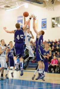 Hunter Benson gets up over Shelby's Michael James and Jeffrey Beckman. Photo/Sherry Wahr