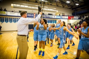 The Mona Shores  team celebrates a district championship with coach Brad Keurth. Photo/Tim Reilly