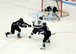 Reeths Puffer's Brandon Young (6) has the puck poke checked away by Shores' Brennen Winegar (21).  Photo/Eric Sturr