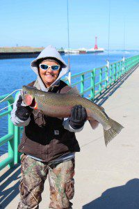 Erin Palmer holds up her 10.70 lb. steelhead on the Pentwater pier. Photo/Jason Goorman
