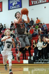 Keegan George glides in for two points as Coopersville's Kyle Gura trails. Photo/Carol Cooper