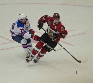 Christian Wolanin brings the puck up the ice as Team USA's No. 39 Joey Andreson goes for the hook. Photo/Marc Hoeksema