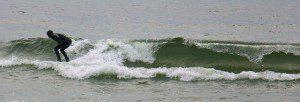 Joe Kostrzewa catches a wave on his surfboard. Photo/Jason Goorman