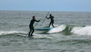 Marc Hoeksema rides a wave as Chris Mattesson paddles out. Photo/Jason Goorman