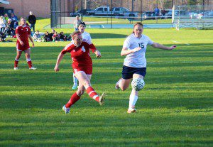 Andie Kriger kicks the ball for Spring Lake as Fruitport's No. 15 Marisa Carmean trails. Photo/Jason Goorman