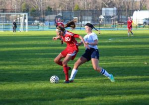 Spring Lake's Saebryn Peel (left) controls the ball as Fruitport's Emily Pieczynski pressures from behind. Photo/Jason Goorman