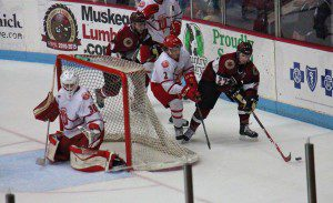 Muskegon's Max Humitz brings the puck around the  Dubuque net as No. 2 Wyatt Ege looks to defend.