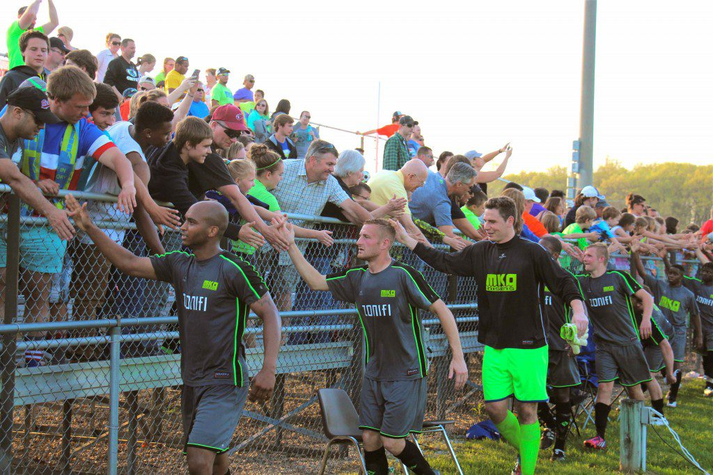 Fans line up to give the Muskegon Risers a highfive after winning their first ever match. Photo/Jason Goorman