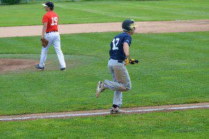 MCC's Anthony Woodard (No. 12) runs to first base with Red Hawk pitcher and Whitehall grad Jake Gillhespy in the background. Photo/Marc Hoeksema
