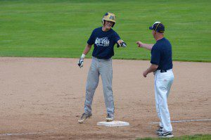Muskegon Catholic's Anthony Woodard fist bumps North Muskegon first base coach Warren Kent. Photo/Marc Hoeksema