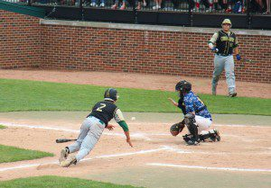 Anthony Woodard dives headfirst into home plate to score as MCC's Jacob Holt watches from on deck. Photo/Jason Goorman