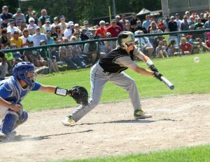 Muskegon Catholic's Devin Combes lays down a bunt that scored a run on a throwing error. Photo/Scott Stone
