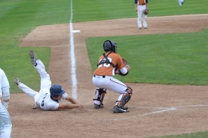 Adrian Anderson slides headfirst into home plate to score Muskegon's first run. photo/Marc Hoeksema