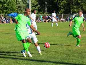 Jeff McClure sends a drop pass during first-half action for the Muskegon Risers. Photo/Jason Goorman