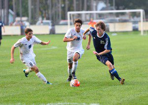 Fruitport's Noah Hendrix (19) is pursued by Mona Shores' Cam Erndteman (9) and Eric Conley (10) on Sept. 1. Photo/Eric Sturr