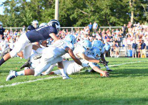Mona Shores' Spencer Stube recovers an early Fruitport fumble. Photo/Eric Sturr