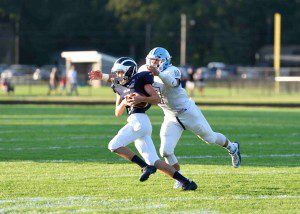 Fruitport's Seth Glover (3) makes the reception as he is hauled down by Tyler Trovinger (7). Photo/Eric Sturr