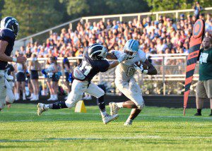 Kobe Burse (6) fends off Matt Sander (11) to get into the end-zone for the third Mona Shores TD. Photo/Eric Sturr.