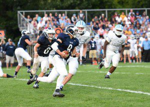Fruitport QB Jarod Wierengo (9) runs to the outside being pursued by Nick Brown (65). Photo/Eric Sturr