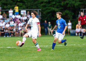 With Anthony Sowles on his heels, Reeths Puffer's Noah Sorn passes the ball to the outside. Photo/Eric Sturr