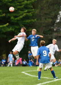 Reeths Puffer's Noah Sorn leaps high for the header over Mona Shores' Colin Vaughan. Photo/Eric Sturr