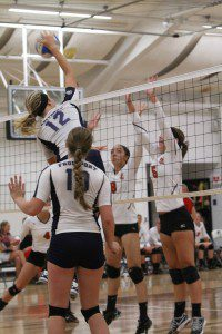Eliza Veihl spikes the ball for Fruitport as No. 8 Lauren Hellman and No. 5 Olivia Grimmer try to block for Spring Lake. Photo/Carol Cooper