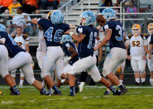 Mona Shores quarterback Elijah Wilson drops back for the pass. Photo/Marc Hoeksema