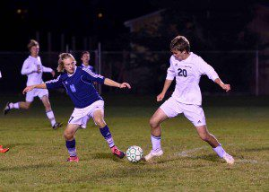 Mona Shores' Bryce Stone and Reeths Puffer's Matthew Udell battle for possession. Photo/Eric Sturr