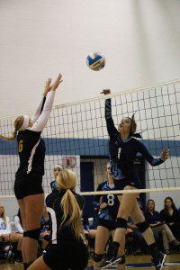 Mona Shores middle hitter Madison Dunn lofts a quick shot over the net. Photo/Jason Goorman