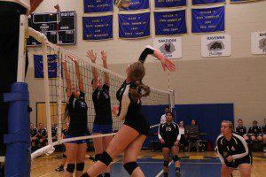 Hart's No. 12 Baylee Draper winds up for the spike while Ravenna's No. 5 Megan Crowley and No. 6 Amber Jacob reach up for the block. Photo/Steve Markel
