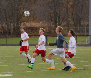 Spring Lake's Brad Debien, Alec Palmer and Ryan Zietlow race an East Lansing player to the ball. Photo/Dave Hart.