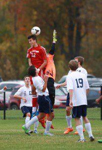 Spring Lake's Ben Mast gets up for the header against Fruitport goalie Connor Werschem. Photo/Kevin Sielaff