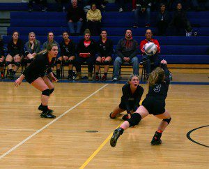 Andie Bolles reaches for the Whitehall dig as No. 10 Julie Brown and No. 14 Brianna Copley react. Photo/Steve Markel