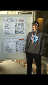 Karina VanDuinen stands next to the leader board at the Division 2 golf state finals.