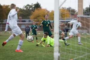 WMC's No. 8 Evan Fles sneaks a pass to Owen Alfree past Crusader goalie Connor O'Neil. Photo/Randy Riksen