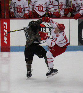 Trevor Hamilton delivers a bone crunching check to Dubuque's Dallas Gerads. Photo/Jason Goorman