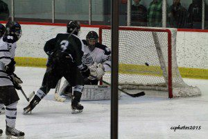 Reeths-Puffer's No. 3 Cole Charlesworth closes in on Mona Shores goalie Anthony Shrum. Photo/Carol Cooper