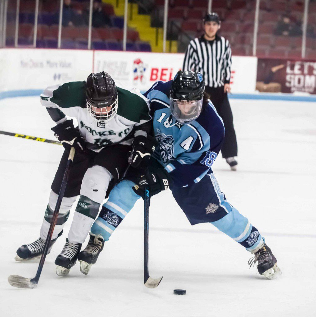 Reeths-Puffer's Collin Powers fights for the puck against Shores' Conner Edlund. Photo/Tim Reilly