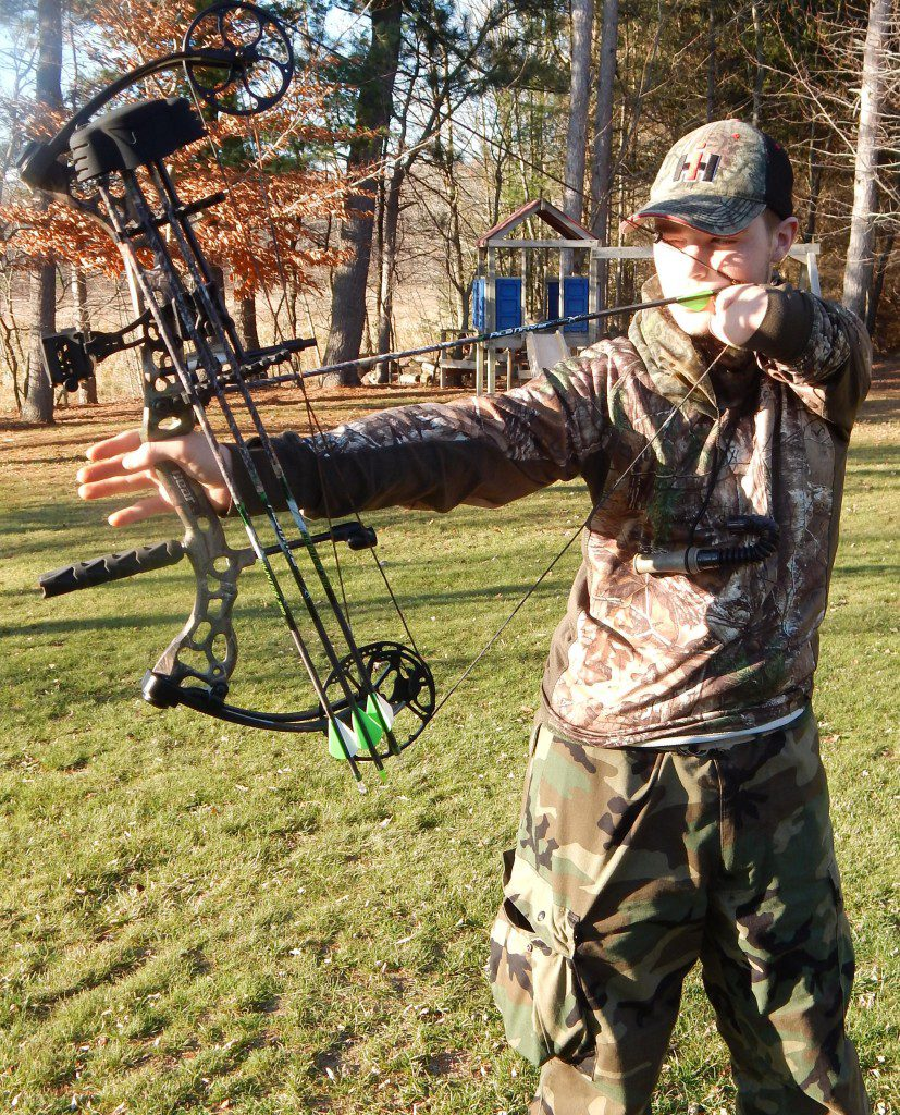 Karson Kriger pulls back his bow and arrow during a practice session.