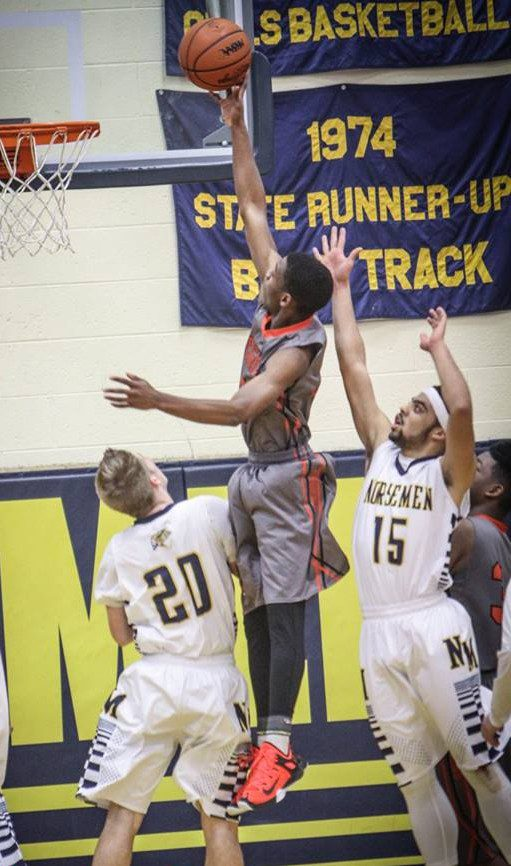 Deondre Wilson goes up two points against North Muskegons No. 20 Dalton Fuller and No. 15 Vernonell Smith. Photo/Joe Lane
