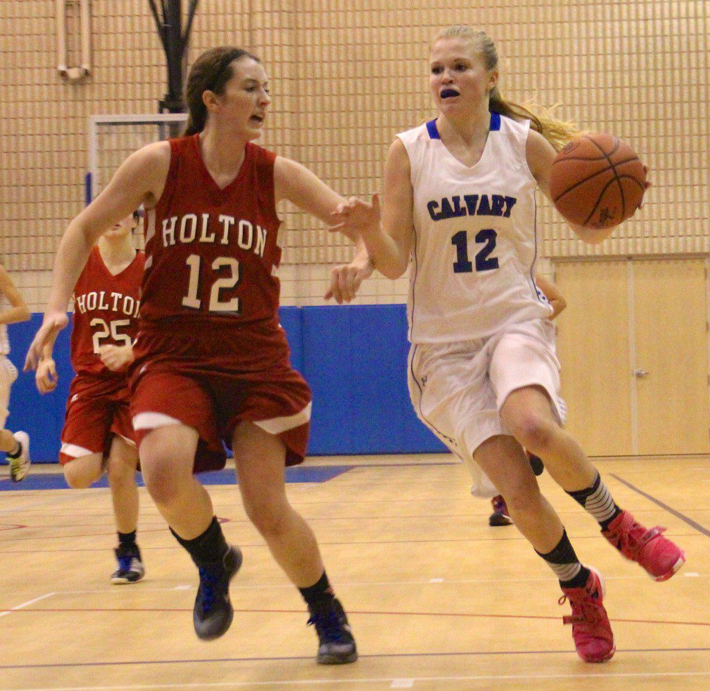 Madison Heiss drives to the basket against Holton's Shelbey Younts. Photo/Jason Goorman
