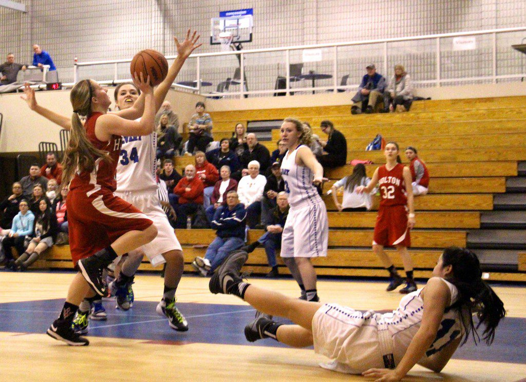 Fruitport Calvary's Kyleah Sutherland takes the charge against Holton guard Makayla Hutchison. Photo/Jason Goorman