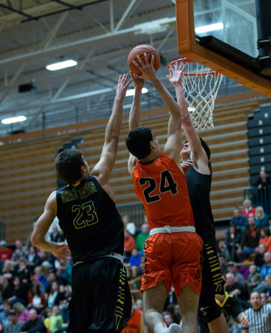 Michael Peterson (24) attempts to dunk but is blocked by Grand Haven's Zac Holman. Photo/Kevin Sielaff