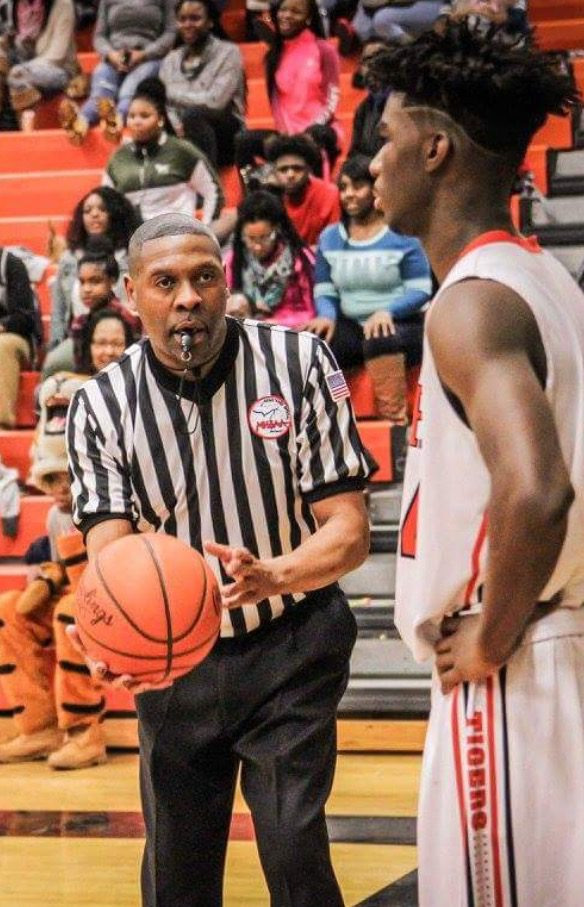 Referee Johnny Tanner hands the ball to DeKari Brown on the Muskegon Heights inbound. Photo/Joe Lane