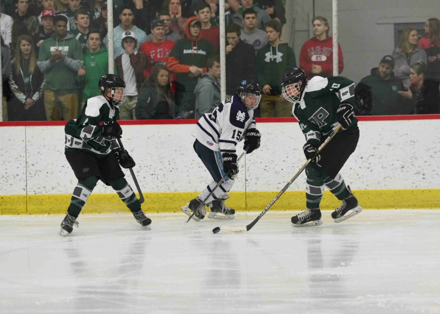 Reeths Puffer's Mason Convertini (10) skates the puck past Monas Shores' Spencer Anderson (15). (photo/Eric Sturr)
