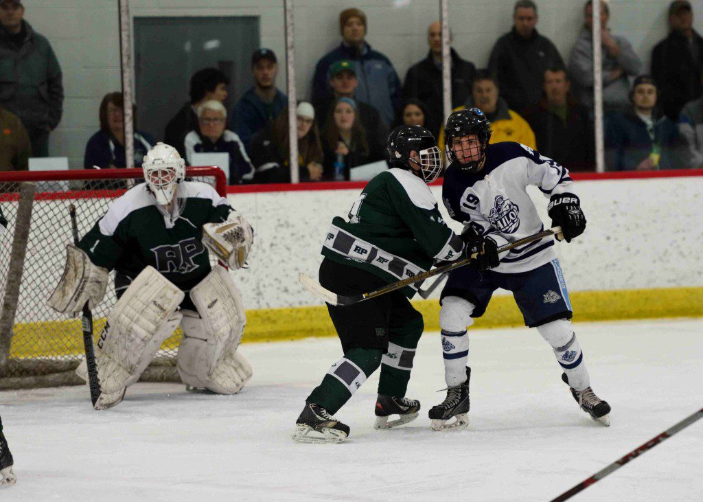 Mona Shores' Zach Tilden (19), and Reeths Puffer's Riley Trautner (14) tangle in front of the net during a Mona Shores power play. (Photo/Eric Sturr)