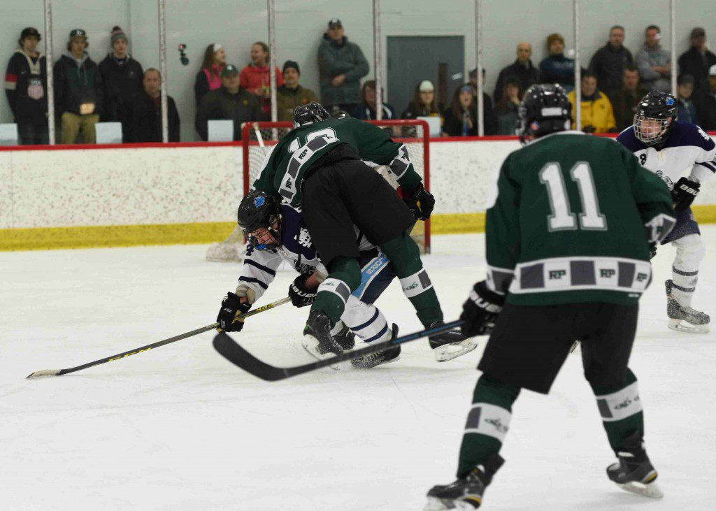 Mona Shores' Nick Nawrocki upends Reeths Puffer's Brody Vanderlinde (12) with a perfect hip check. (photo/Eric Sturr)